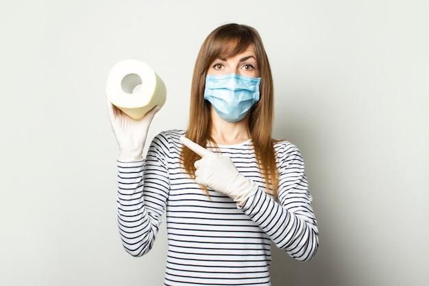 Jong meisje in een medisch masker en medische handschoenen met een rol wc-papier en wijst een vinger naar haar op een lichte muur. concept quarantaine, tekort, paniek