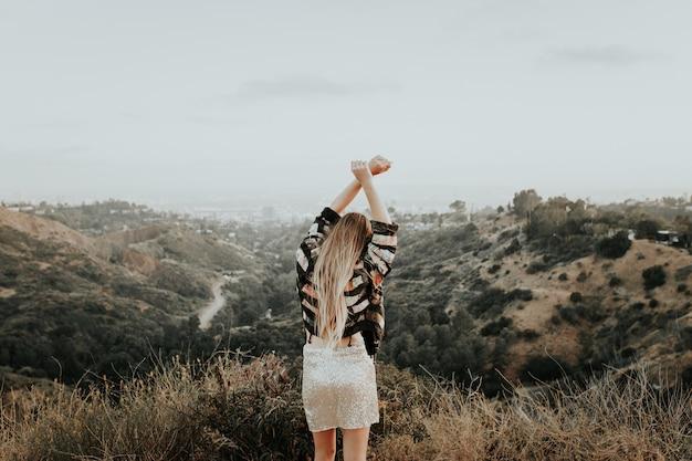 Jong meisje in een mooie outfit bovenop de berg