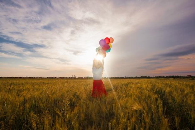 Jong meisje in een rode rok met gekleurde ballonnen in tarweveld. natuurinspiratie, tegenlicht