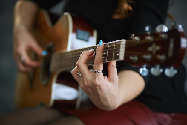 Jong meisje in een rood lederen minirok en zwarte panty gitaar spelen