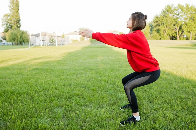 Jong meisje in een rood sportjack gaat sporten in het stadion