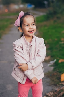 Jong meisje in een roze jas en roze legging in het park