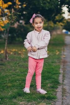 Jong meisje in een roze jasje en roze beenkappen in het park.