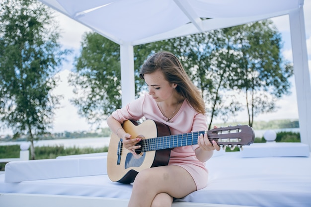 Jong meisje in een roze jurk met een gitaar