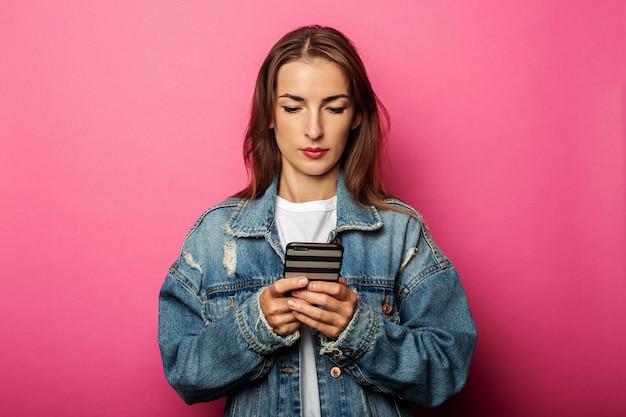 Jong meisje in een spijkerjasje kijkt naar de telefoon