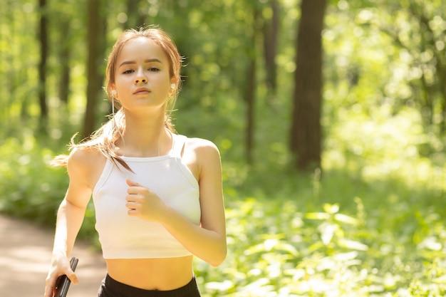 Jong meisje in een sportuniform rent 's ochtends in het park