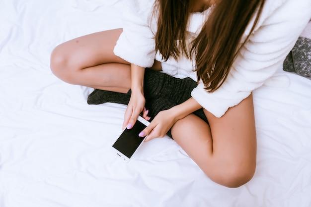 Jong meisje in een wit gewaad en warme sokken zittend op het bed met een telefoon