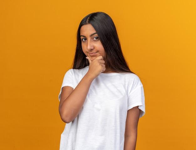 Jong meisje in een wit t-shirt dat naar de camera kijkt met een peinzende uitdrukking op het gezicht met de hand op haar kin die over oranje staat