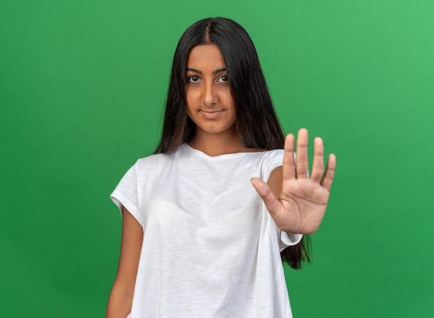 Jong meisje in een wit t-shirt dat naar de camera kijkt met een zelfverzekerde glimlach op het gezicht en een stopgebaar maakt met de hand