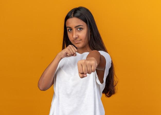 Jong meisje in een wit t-shirt dat naar de camera kijkt met gebalde vuisten die zich voordeed als een bokser die met een serieus gezicht kijkt