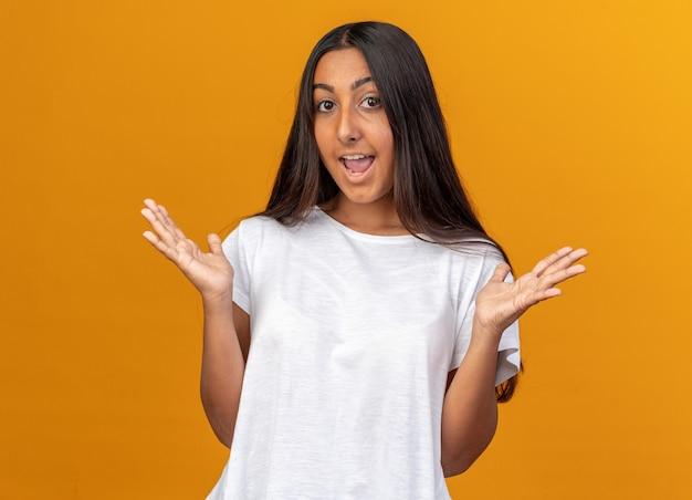 Jong meisje in een wit t-shirt kijkend naar de camera, blij en vrolijk lachend met opgeheven armen over oranje