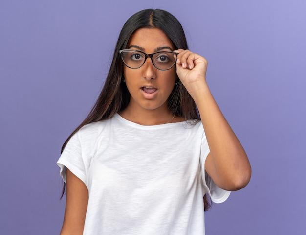 Jong meisje in een wit t-shirt met een bril die naar de camera kijkt, verrast en verbaasd staat over een blauwe achtergrond