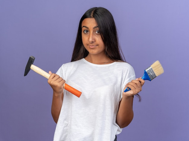 Jong meisje in een wit t-shirt met een hamer en een kwast die naar de camera kijkt met een zelfverzekerde glimlach op het gezicht dat over blauw staat