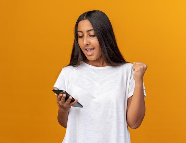 Jong meisje in een wit t-shirt met een smartphone die ernaar kijkt en de vuist balt, blij en opgewonden