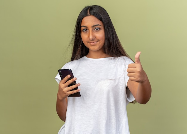 Jong meisje in een wit t-shirt met een smartphone die naar een camera kijkt die lacht en duimen opsteekt terwijl ze over een groene achtergrond staan