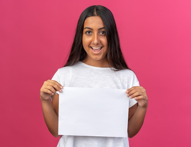 Jong meisje in een wit t-shirt met een wit blanco vel papier kijkend naar de camera met een glimlach op het gezicht dat over roze staat