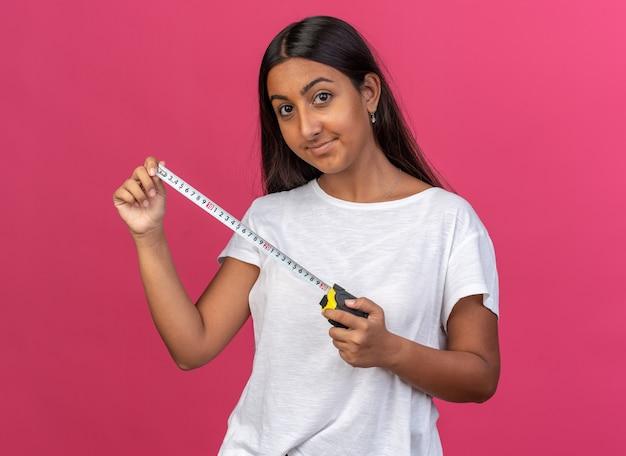 Jong meisje in een wit t-shirt met meetlint dat naar de camera kijkt met een glimlach op het gezicht, blij en positief