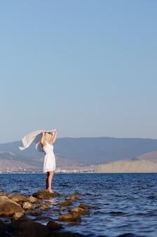 Jong meisje in een witte jurk met een witte zakdoek aan de zee