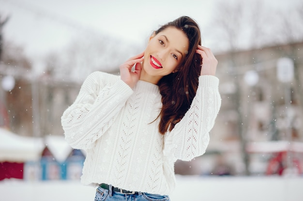 Jong meisje in een witte sweater die zich in een de winterpark bevindt