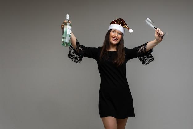Jong meisje in feestelijk masker met cadeau en fles wijn viert vakantie op grijze achtergrond met confetti, kopieer ruimte