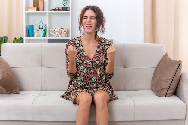 Jong meisje in gebloemde jurk blij en opgewonden vuisten gebald en verheugd over haar succes zittend op een bank in lichte woonkamer living