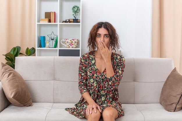Jong meisje in gebloemde jurk die verbaasd en verrast kijkt, zittend op een bank in een lichte woonkamer