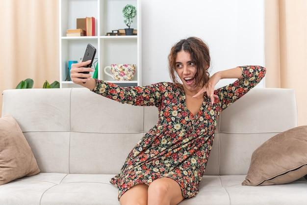 Jong meisje in gebloemde jurk doet selfie met smartphone gelukkig en positief glimlachend vrolijk zittend op een bank in lichte woonkamer