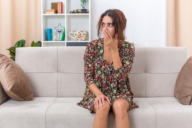 Jong meisje in gebloemde jurk kijkt verbaasd en geschokt opzij en bedekt de mond met de hand zittend op een bank in een lichte woonkamer