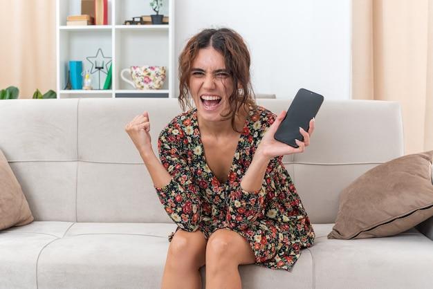 Jong meisje in gebloemde jurk met smartphone blij en opgewonden gebalde vuist verheugt zich over haar succes zittend op een bank in lichte woonkamer