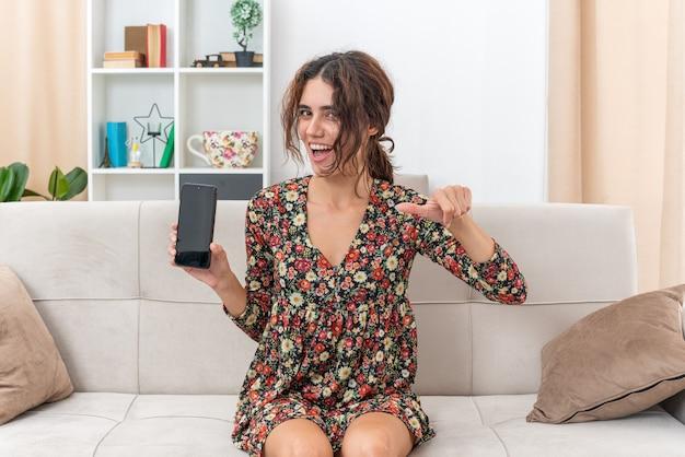 Jong meisje in gebloemde jurk met smartphone die er gelukkig en vrolijk uitziet glimlachend in grote lijnen knipogend met duimen omhoog zittend op een bank in lichte woonkamer