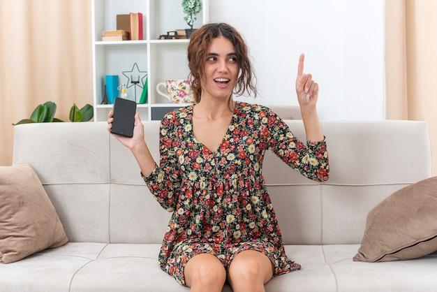 Jong meisje in gebloemde jurk met smartphone die er verrast en blij uitziet en wijsvinger laat zien met een geweldig nieuw idee zittend op een bank in een lichte woonkamer
