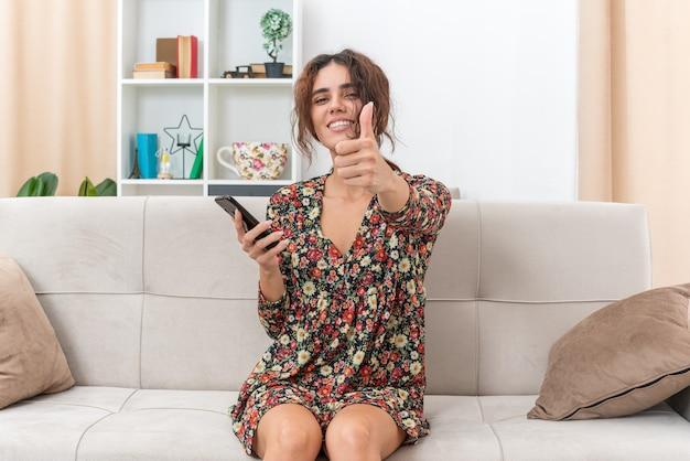 Jong meisje in gebloemde jurk met smartphone glimlachend vrolijk duimen omhoog zittend op een bank in lichte woonkamer living