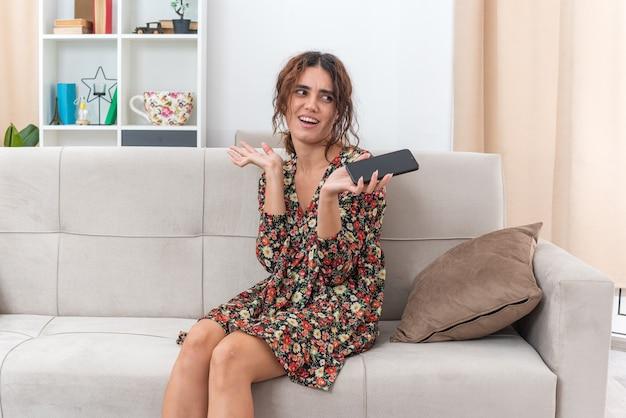Jong meisje in gebloemde jurk met smartphone opzij kijkend glimlachend verward met opgeheven armen zittend op een bank in lichte woonkamer