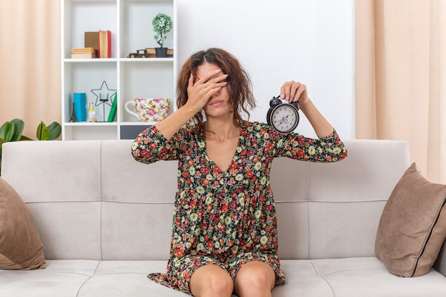 Jong meisje in gebloemde jurk met wekker die ogen bedekt met hand moe en verveeld zittend op een bank in lichte woonkamer