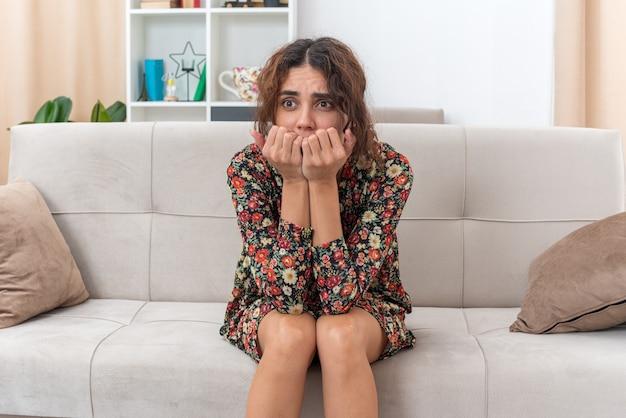 Jong meisje in gebloemde jurk opzij kijkend gestrest en nerveus bijtende nagels zittend op een bank in lichte woonkamer