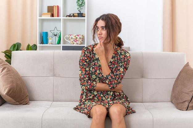 Jong meisje in gebloemde jurk opzij kijkend met peinzende uitdrukking met hand op kin denkend zittend op een bank in lichte woonkamer