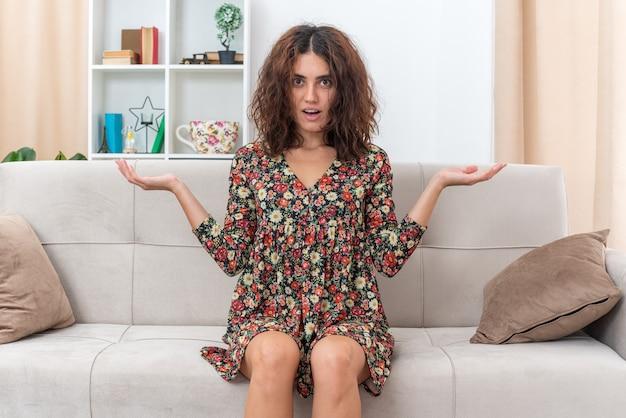 Jong meisje in gebloemde jurk verrast en verward spreidende armen naar de zijkanten zittend op een bank in lichte woonkamer