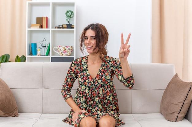 Jong meisje in gebloemde jurk ziet er gelukkig en vrolijk uit met een v-teken dat breed lacht terwijl ze op een bank zit in een lichte woonkamer living