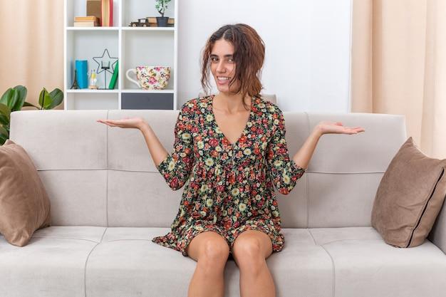 Jong meisje in gebloemde jurk ziet er gelukkig en vrolijk uit met gespreide armen naar de zijkanten glimlachend breed zittend op een bank in lichte woonkamer living