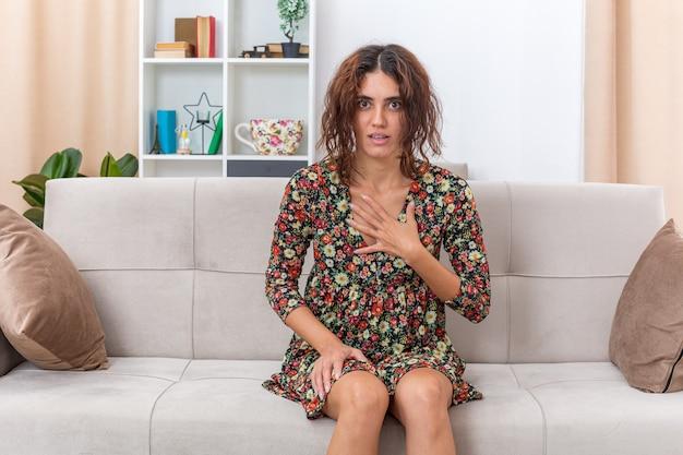 Jong meisje in gebloemde jurk ziet er verward uit terwijl ze de hand op haar borst houdt, zittend op een bank in een lichte woonkamer living