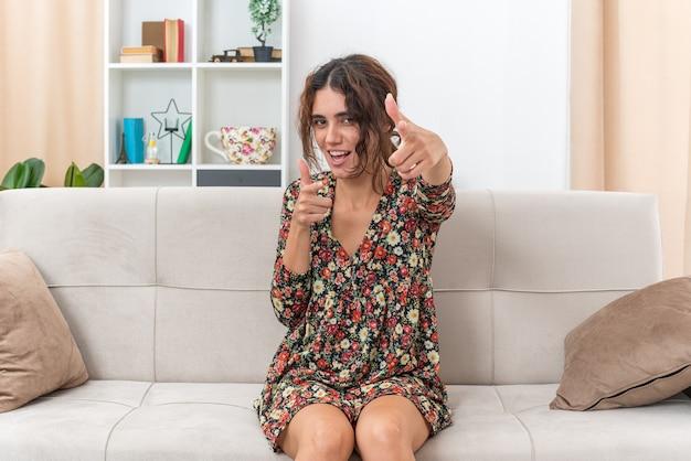 Jong meisje in gebloemde jurk ziet er zelfverzekerd gelukkig en vrolijk lachend uit, wijzend met wijsvingers naar voren, zittend op een bank in lichte woonkamer