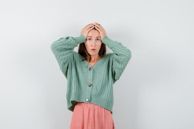Jong meisje in gebreide kleding, rok hand in hand op het hoofd en op zoek verrast, vooraanzicht.