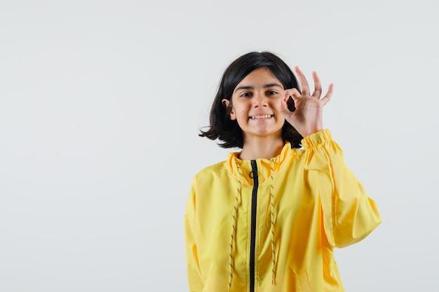 Jong meisje in geel bomberjack dat ok teken toont en gelukkig kijkt