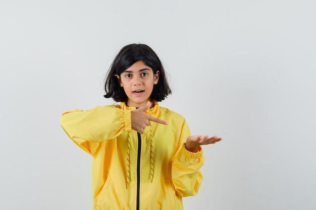 Jong meisje in geel bomberjack die hand uitrekt als iets vasthoudt en ernaar wijst en verbaasd kijkt