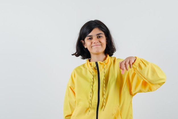 Jong meisje in geel bomberjack die hand uitrekt als iets vasthoudt en gelukkig kijkt
