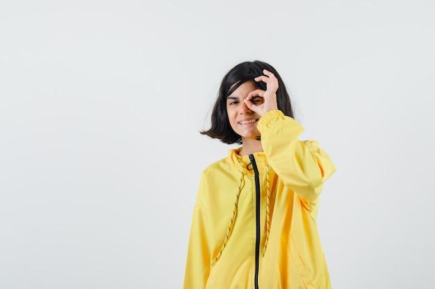 Jong meisje in geel bomberjack die ok teken op oog tonen en gelukkig kijken