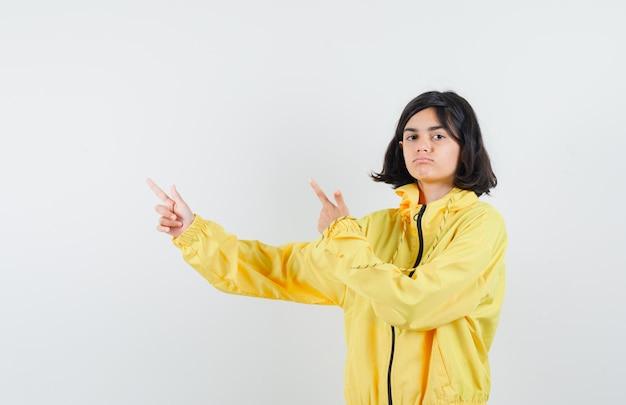 Jong meisje in geel bomberjack en roze rok die met wijsvingers naar links wijst en er serieus uitziet