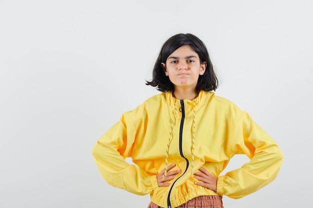 Jong meisje in geel bomberjack hand in hand op taille, wangen puffend en op zoek geïrriteerd