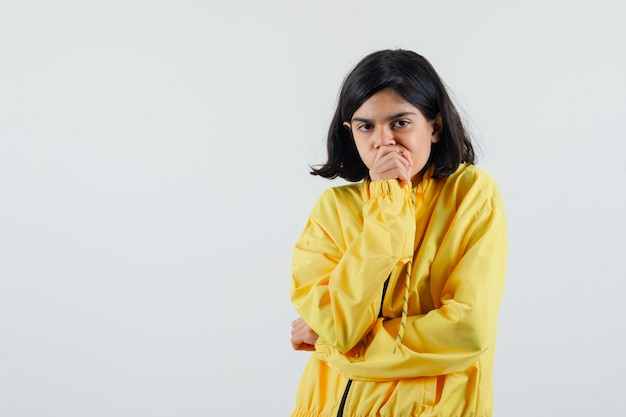 Jong meisje in geel bomberjack hand op de mond houden, vuist balanceren en aan iets denken en peinzend kijken