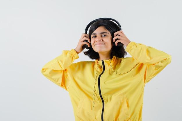 Jong meisje in geel bomberjack, luisteren naar muziek met een koptelefoon en glimlachen en kijken gelukkig